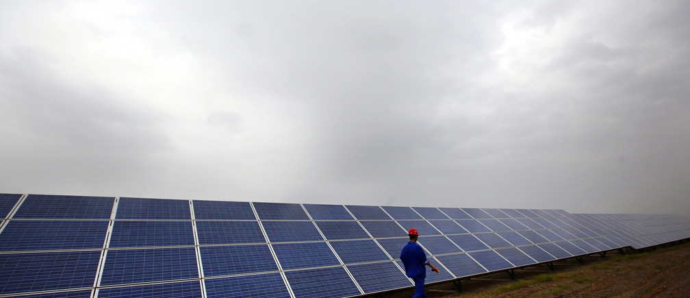 A worker inspects solar panels at a solar farm in Dunhuang, 950km (590 miles) northwest of Lanzhou, Gansu Province September 15, 2013. China is pumping investment into wind power, which is more cost-competitive than solar energy and partly able to compete with coal and gas. China is the world's biggest producer of CO2 emissions, but is also the world's leading generator of renewable electricity. Environmental issues will be under the spotlight during a working group of the Intergovernmental Panel on Climate Change, which will meet in Stockholm from September 23-26. REUTERS/Carlos Barria  (CHINA - Tags: ENERGY BUSINESS ENVIRONMENT) - GM1E99M17XD01