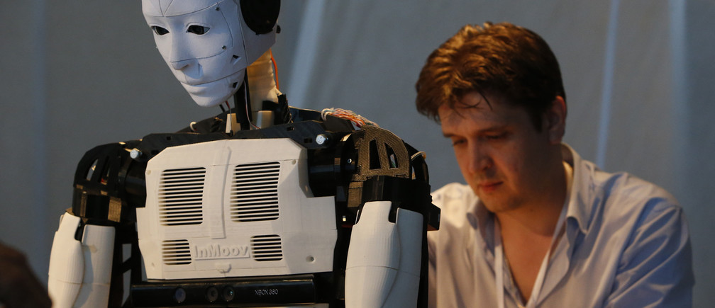 """A technician makes adjustments to the """"Inmoov"""" robot from Russia during the """"Robot Ball"""" scientific exhibition in Moscow May 17, 2014. Picture taken May 17, 2014. REUTERS/Sergei Karpukhin (RUSSIA - Tags: SCIENCE TECHNOLOGY SOCIETY) - RTR3PNJ5"""