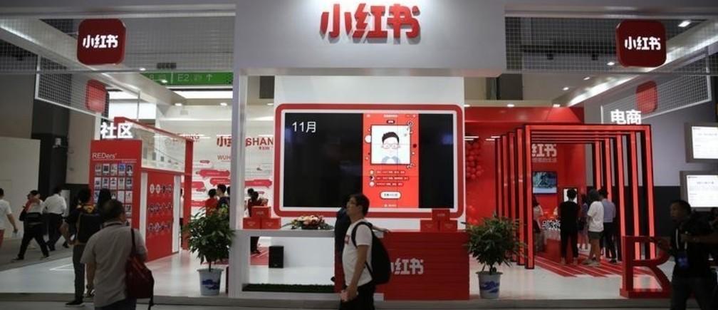 "A man walks past the booth of Chinese startup Xiaohongshu, which means ""little red book"" in Chinese, at the Big Data Expo in Guiyang, Guizhou province, China May 27, 2019. Picture taken May 27, 2019. REUTERS/Stringer  ATTENTION EDITORS - THIS IMAGE WAS PROVIDED BY A THIRD PARTY. CHINA OUT. - RC1B796CDF60"
