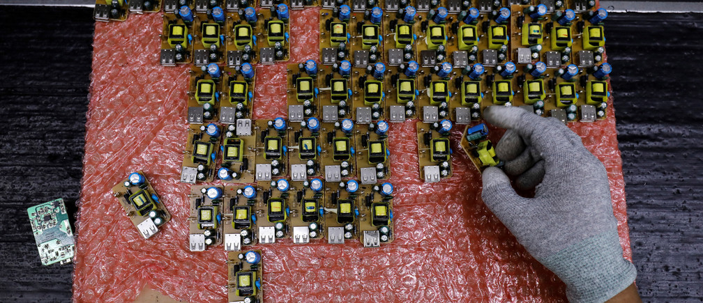 A worker arranges battery charger circuit boards at a mobile phone battery manufacturing plant in Noida, India, October 12, 2018. Picture taken October 12, 2018. REUTERS/Anushree Fadnavis - RC118A511050