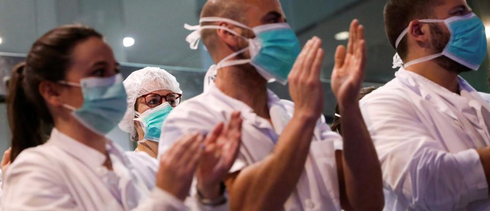 Los trabajadores de la salud del Hospital Clínico aplauden a la ciudadanía que les muestra su gratitud desde sus balcones y ventanas, durante el brote de la enfermedad coronavirus (COVID-19), en Barcelona, España, el 24 de marzo de 2020.