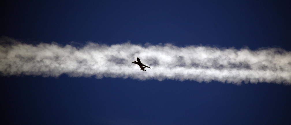 An aeroplane flies underneath the jet stream of another aircraft above the Italian city of Padua.