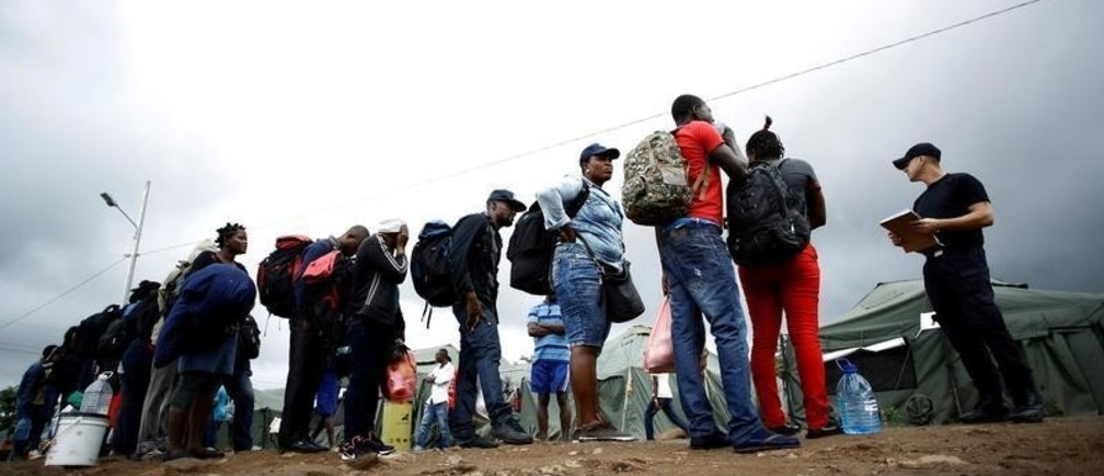 An official of migration gives instructions to a group of Haitian and Africans migrants stranded in Costa Rica, who arrived at a makeshift camp at the border between Costa Rica and Nicaragua, in La Cruz, Costa Rica, December 20, 2016. Picture taken December 20, 2016.  REUTERS/Juan Carlos Ulate - RTX2W2TC