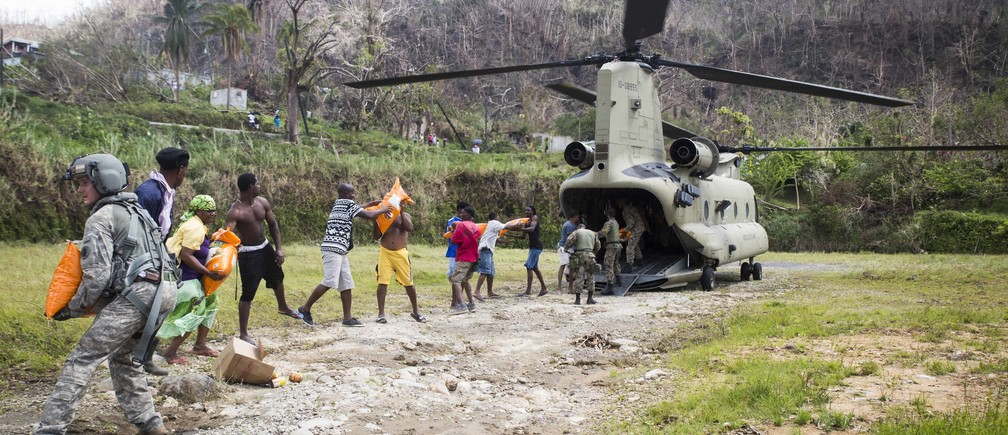 U.S. Army Sgt. Delton Reynolds, left, a flight engineer with Joint Task Force - Leeward Islands, joins a chain with local residents and members of the Jamaican Defence Force to unload relief supplies from a CH-47 Chinook helicopter at Wotten Waven, Dominica, Oct. 3, 2017. The aircraft delivered rice and kitchen sets from the U.S. Agency for International Development to the community. At the request of USAID, JTF-LI has deployed aircraft and service members to assist in delivering relief supplies to Dominica in the aftermath of Hurricane Maria. The task force is a U.S. military unit composed of Marines, Soldiers, Sailors and Airmen, and represents U.S. Southern Command's primary response to the hurricanes that have affected the eastern Caribbean. (U.S. Marine Corps photo by Sgt. Ian Leones)
