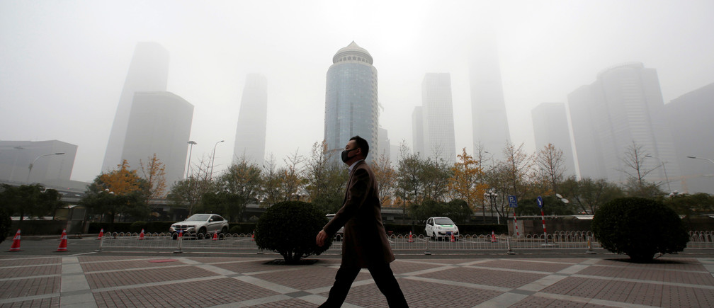 A man wearing a mask walks in the central business district on a polluted day after a yellow alert was issued for smog, in Beijing, China November 14, 2018.  REUTERS/Jason Lee     TPX IMAGES OF THE DAY - RC18AC195000