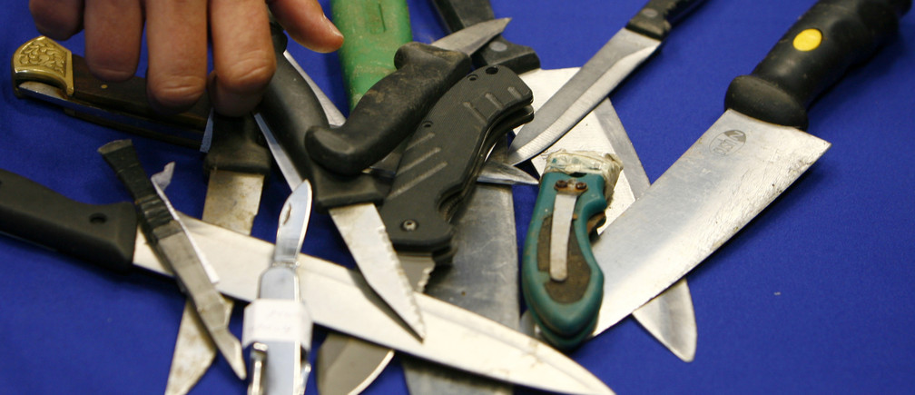 A Metropolitan Police representative arranges knives, seized in recent operations, for photographers after a news conference about knife crime, at New Scotland Yard, in central London on May 29, 2008.