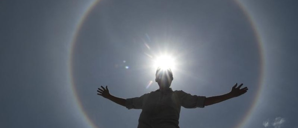 A man poses for photos as solar halo is seen in the sky of Brasilia September 30, 2011.  This weather phenomenon creates rainbows around the sun, and according to meteorologist, halo is formed by the reflection of ice crystals.  REUTERS/Ueslei Marcelino (BRAZIL - Tags: ENVIRONMENT TPX IMAGES OF THE DAY) - RTR2S1UT