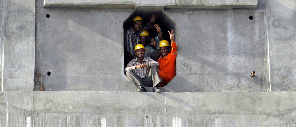 Workers watch the final concrete slab of the first phase of construction being placed of at the construction site of the Bandra-Worli sea link in Mumbai, April 28, 2009. The first phase of construction of Bandra-Worli sea link, an eight-lane, cable-stayed bridge above the Arbian sea was completed on Tuesday and it will be opened to commuters on later next month. The 4.7 km bridge which links Worli and Bandra areas of the city is expected to ease out traffic in the congested Mumbai. REUTERS/Arko Datta (INDIA BUSINESS TRANSPORT) - GM1E54T0I4C01