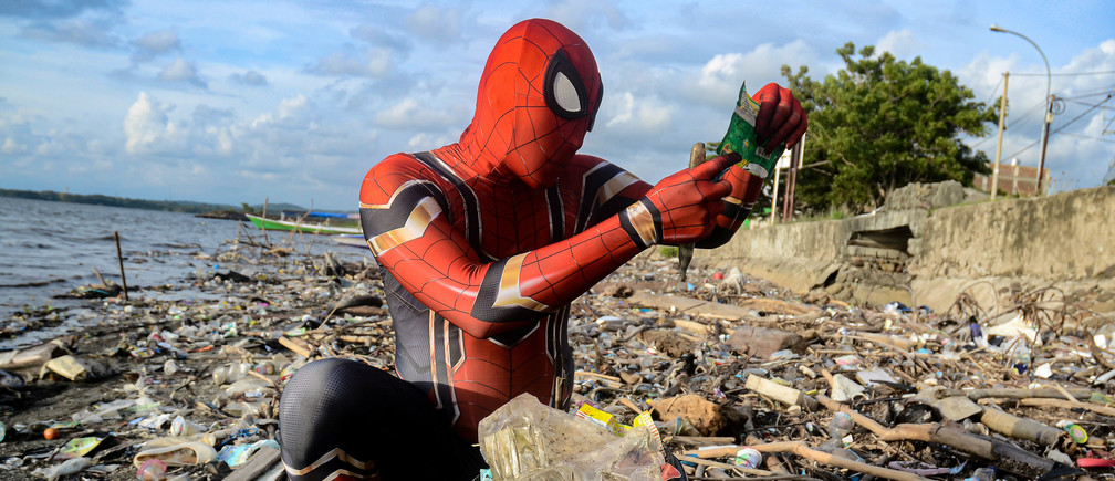 Rudi Hartono, a man dressed in Spider-Man costume, looks at plastic waste as he collects rubbish at a beach in Pare-Pare, South Sulawesi province, Indonesia, January 18, 2020. Picture taken January 18, 2020. REUTERS/Stringer     TPX IMAGES OF THE DAY - RC20YE9QNFAR