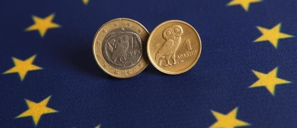 An one Euro (L) and one Greek Drachma coins are displayed on an European flag in this picture illustration taken in Istanbul June 14, 2012. On Sunday, Greece votes in an election where a radical left party that opposes the strict terms of the country's bailout could emerge victorious, increasing the chances of it abandoning the euro and returning to the drachma. REUTERS/Murad Sezer (TURKEY - Tags: POLITICS BUSINESS) - GM2E86E1OQ601