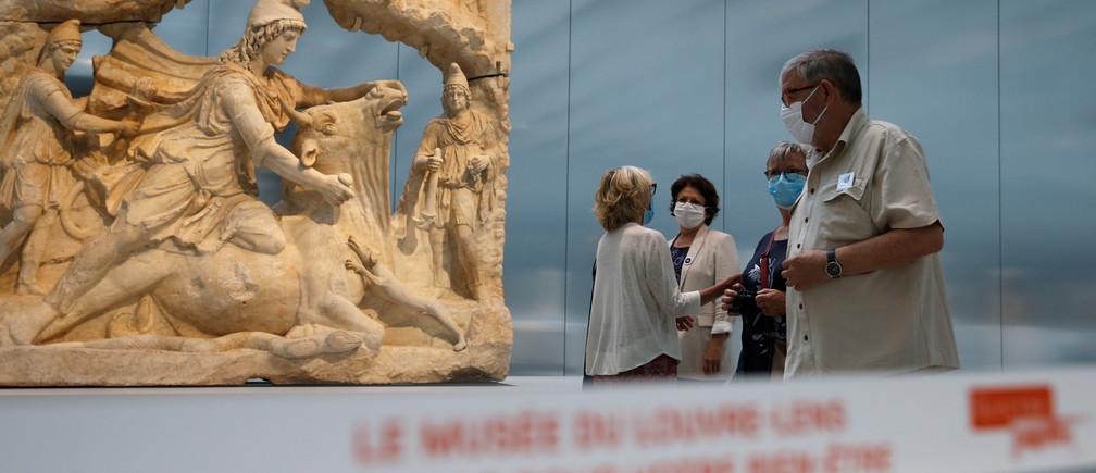 """Los visitantes, con máscaras protectoras, caminan entre las esculturas de la """"Galerie du Temps"""" (Galería del Tiempo) del museo del Louvre Lens durante su reapertura en Lens, ya que los museos franceses reabren con medidas de seguridad tras el brote de la enfermedad coronavirus (COVID-19) en Francia, el 3 de junio de 2020."""