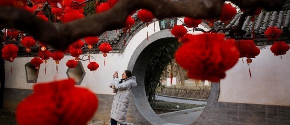 A woman takes pictures of trees decorated for Spring Festival ahead of the Chinese Lunar New Year at Ditan Park in Beijing, China February 11, 2018. REUTERS/Thomas Peter