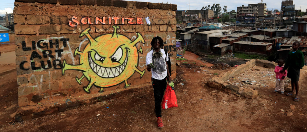 Brian Musasia Wanyande, an artist from the Mathare Roots's youth group, walks away after painting an advocacy graffiti against the spread of the coronavirus disease in Mathare, Nairobi, Kenya, April 2020.