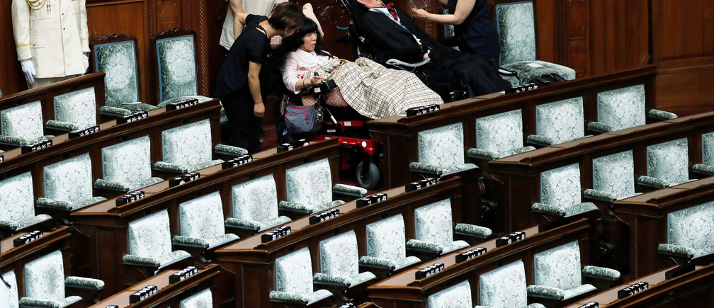 Reiwa Shinsengumi party's disabled lawmaker Yasuhiko Funago, who has amyotrophic lateral sclerosis (ALS), and Eiko Kimura, who has cerebral palsy, prepare to leave the hall after attending the opening of an extraordinary session of parliament in Tokyo, Japan, August 1, 2019. REUTERS/Kim Kyung-Hoon - RC11BD237100