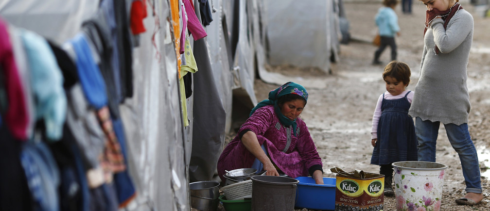 A refugee woman washes dishes at a refugee camp.