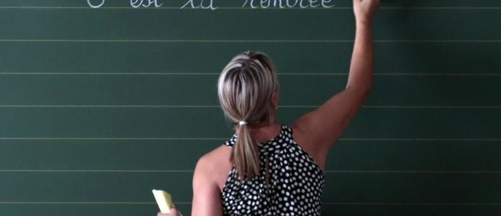 "A teacher writes the phrase ""Today it is the start of the new school year"" on the blackboard of her classroom on the first day of the new school year at a primary school in Nice, September 3, 2013.    REUTERS/Eric Gaillard (FRANCE - Tags: EDUCATION) - PM1E99314PA01"
