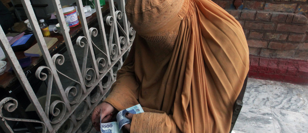 A woman, clad in burqa, counts cash she received from a counter of Ehsaas Emergency Cash program, introduced by the government for vulnerable families due to the spread coronavirus disease (COVID-19), in Peshawar, Pakistan April 9, 2020. REUTERS/Khuram Parvez - RC231G9M7K7Z