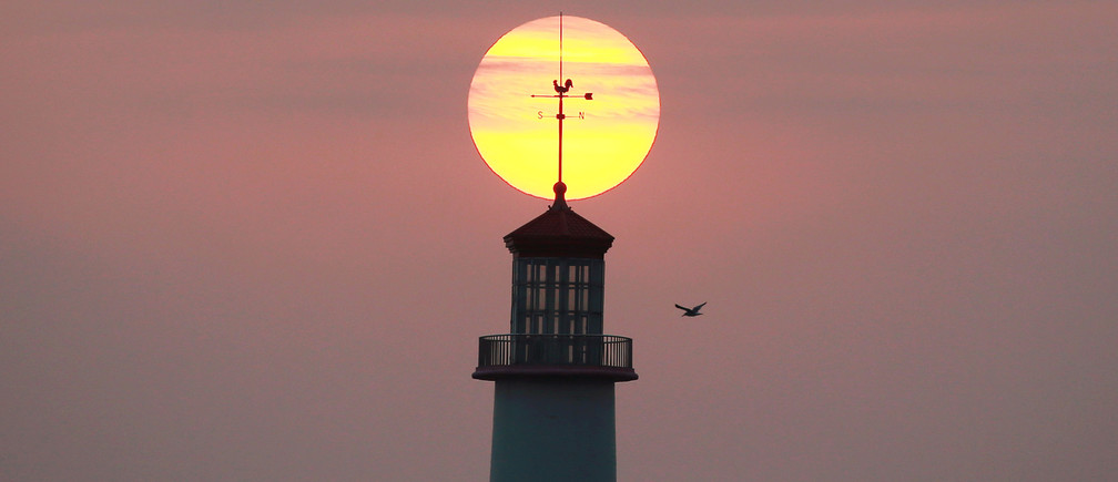 The sun sets behind a lighthouse in Dalian, Liaoning province, China September 29, 2018. Picture taken September 29, 2018. REUTERS/Stringer  ATTENTION EDITORS - THIS IMAGE WAS PROVIDED BY A THIRD PARTY. CHINA OUT. - RC136E3704C0
