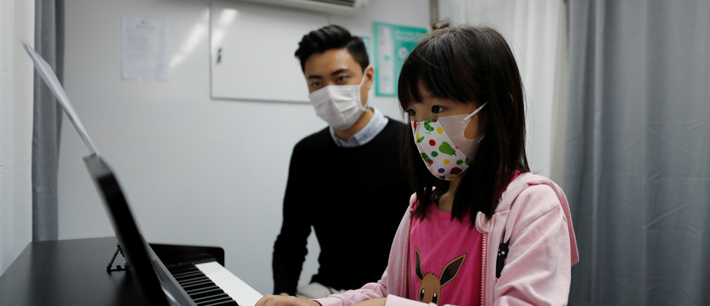 Sophia Cheung, a 7-year-old student, practices piano next to Curriculum officer Evan Kam in Hong Kong, China, on 3 April 2020.