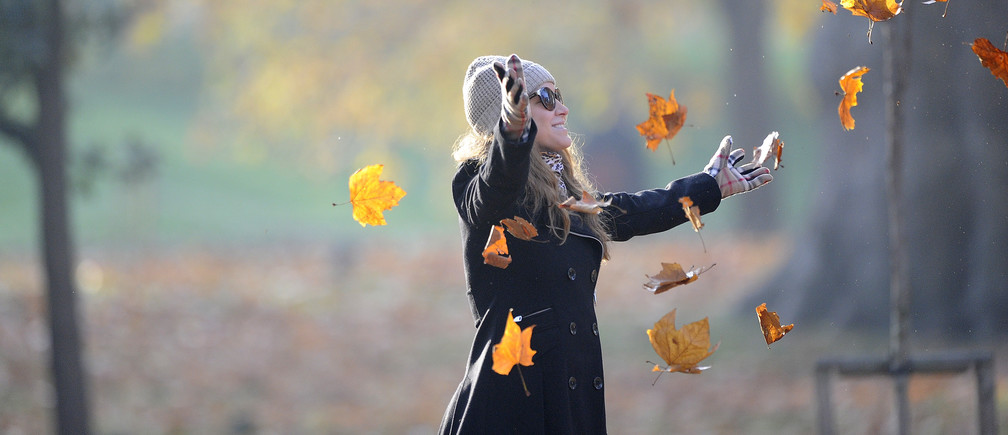A woman throws leaves as her friend takes a photograph of her in St James's park, London, November 20, 2011.