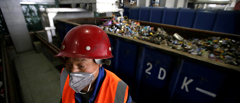 A worker stands next to kitchen waste at a garbage transfer station in Beijing, China March 30, 2017. Picture taken on March 30, 2017. REUTERS/Jason Lee - RTX33IGE