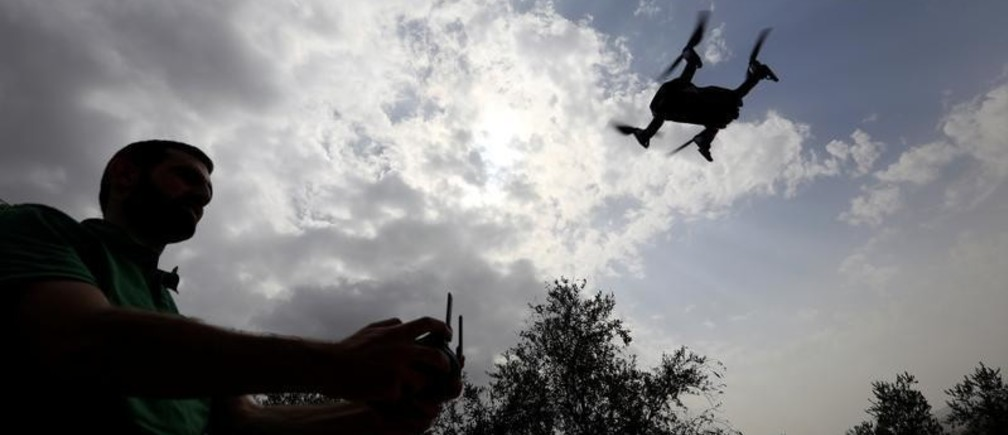 A man operates a drone over olive trees in Nabatieh area, Lebanon October 25, 2018. REUTERS/ Jamal Saidi - RC14B511DAF0