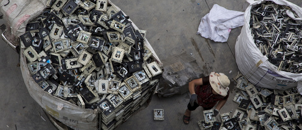 A worker distributes electronic waste at a government managed recycling centre at the township of Guiyu in China's southern Guangdong province June 10, 2015. The town of Guiyu in the economic powerhouse of Guangdong province in China has long been known as one of the world's largest electronic waste dump sites. At its peak, some 5,000 workshops in the village recycle 15,000 tonnes of waste daily including hard drives, mobile phones, computer screens and computers shipped in from across the world. Many of the workers, however, work in poorly ventilated workshops with little protective gear, prying open discarded electronics with their bare hands. Plastic circuit boards are also melted down to salvage bits of valuable metals such as gold, copper and aluminum. As a result, large amounts of pollutants, heavy metals and chemicals are released into the rivers nearby, severely contaminating local water supplies, devastating farm harvests and damaging the health of residents. The stench of burnt plastic envelops the small town of Guiyu, while some rivers are black with industrial effluent. According to research conducted by Southern China's Shantou University, Guiyu's air and water is heavily contaminated by toxic metal particles. As a result, children living there have abnormally high levels of lead in their blood, the study found. While most of the e-waste was once imported into China and processed in Guiyu, much more of the discarded e-waste now comes from within China as the country grows in affluence. China now produces 6.1 million metric tonnes of e-waste a year, according to the Ministry of Industry and Information Technology, second only to the U.S with 7.2 million tonne