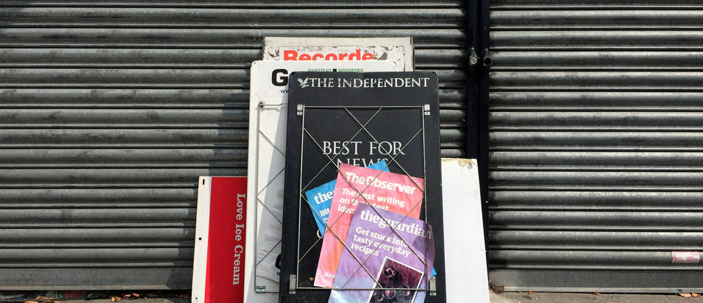 Disused advertising boards for news papers are left against the shutters of a closed down news agent's shop in London, Britain, August 29, 2016. REUTERS/Russell Boyce  - D1BETYFMXHAB