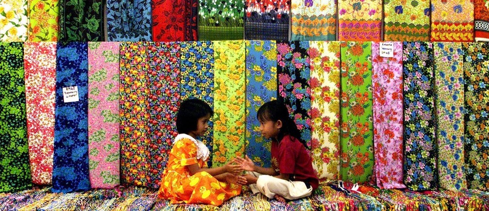 Five-year-old Ririn Faria (L) and her sister Baiduri play among batik at the family's shop in Kuala Lumpur December 22. Batik, a textile design which uses dyeing and hot wax to paint on cloth, is favoured by Malaysians during the festive season of Eid al-Fitr which falls on either January 7 or 8, depending on the sighting of the moon. The shop's manager said sales have increased by 50 percent ahead of the season. The cloth are sold at 50 ringgit ($13.00) a piece. Moslems around the world celebrate Eid al-Fitr after the fasting month of Ramadan.BM/TAN - RTRTK7T