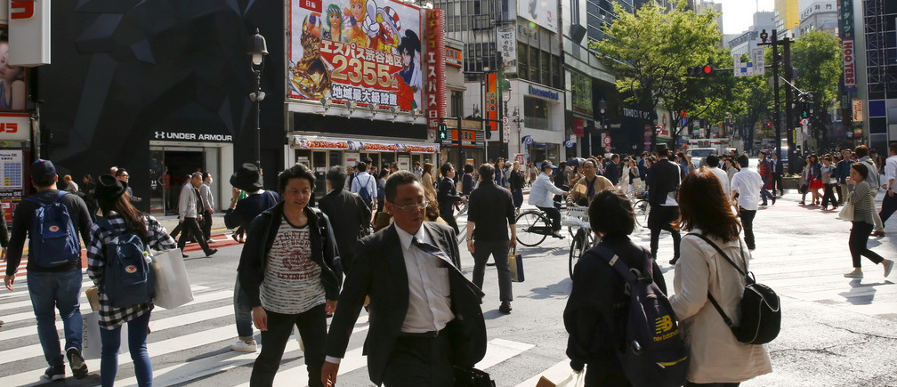 People cross a street in a shopping area in the Shinjuku district in Tokyo