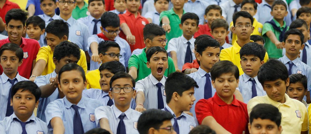 A schoolboy yawns as he and other students take an oath inside a school in Ahmedabad, India