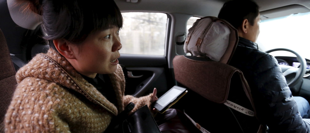 "Yoko Wu instructs an Uber taxi driver en route to her office in Beijing, China, November 18, 2015. Yoko lives in the Beijing suburbs with her family and children. Uber has become her main way to beat traffic and get work done on the road.   REUTERS/Kim Kyung-Hoon   PICTURE 27 OF 36 - SEARCH ""EARTHPRINTS BEIJING"" FOR ALL IMAGES - RTX1VXHN"