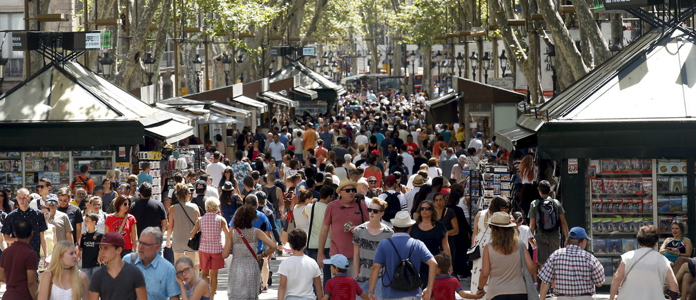 People walk by Las Ramblas in Barcelona, Spain, August 16, 2015. Barcelona's new mayor is picking a fight with home rental websites as she tries to crack down on uncontrolled tourism that she fears could drive out poor residents and spoil the Catalan capital's charm. Picture taken on August 16, 2015. REUTERS/Albert GeaATTENTION EDITORS: SPANISH LAW REQUIRES THAT THE FACES OF MINORS ARE MASKED IN PUBLICATIONS WITHIN SPAIN. - GF10000182225
