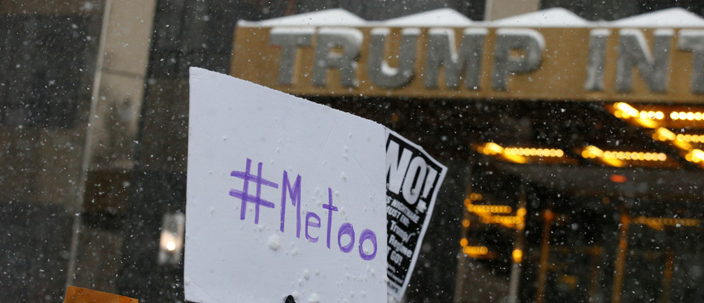 Protest signs are raised at #MeToo demonstration outside Trump International hotel in New York City, NY, U.S., December 9, 2017. REUTERS/Brendan McDermid - RC1939B6C700