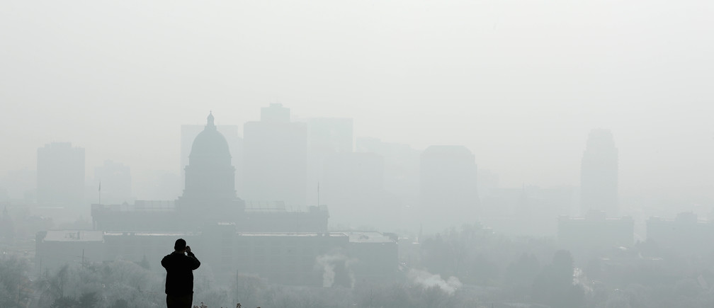 A man stops to take a picture of the Utah State Capitol (L) and buildings that are shrouded in smog in downtown Salt Lake City, Utah, U.S. December 12, 2017. Sometimes during the winter, temperature inversions form in the Salt Lake Valley, when the upper air temperature is warmer than the air on the valley floor, forming a lid, trapping polluted air. REUTERS/George Frey - RC12E3706EB0
