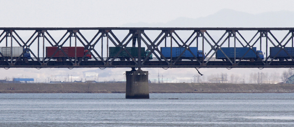 Trucks drive on the Friendship Bridge over the Yalu River which connects North Korea's Sinuiju to China's Dandong, April 11, 2013. China has stepped up checks on shipments to and from North Korea almost two months after agreeing to new U.N. sanctions that demand greater scrutiny of trade, but the flow of goods in and out of the reclusive state appears largely unaffected. Picture taken April 11, 2013. REUTERS/Jacky Chen (CHINA - Tags: BUSINESS POLITICS) - RTXZ5H5