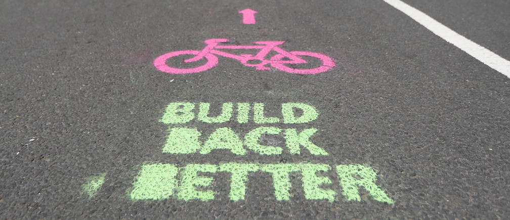 A cyclist cycles by painted stencils on a street to create pop up bike lanes in preparation for distanced bike rides, following the outbreak of the coronavirus disease (COVID-19), London, Britain, May 16, 2020