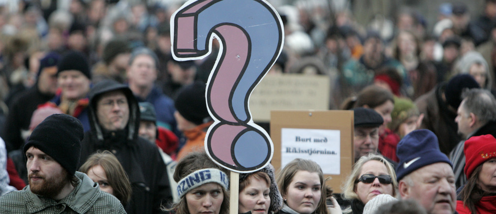 "A woman holds placard during a peaceful protest near Iceland's Parliament house in Reykjavik January 24, 2009. A day after saying he would quit, Iceland's Prime Minister Geir Haarde voiced ""contempt"" on Saturday for some of the actions by banks that triggered the country's economic collapse. Iceland, one of the richest countries in the world in 2007, plunged into crisis in October when it fell victim to the global credit crunch. Its currency collapsed as its financial system imploded. To stay afloat, it negotiated a $10 billion aid package crafted by the International Monetary Fund and effectively froze trade in its currency.     REUTERS/Ints Kalnins (ICELAND) - GM1E51P036S01"