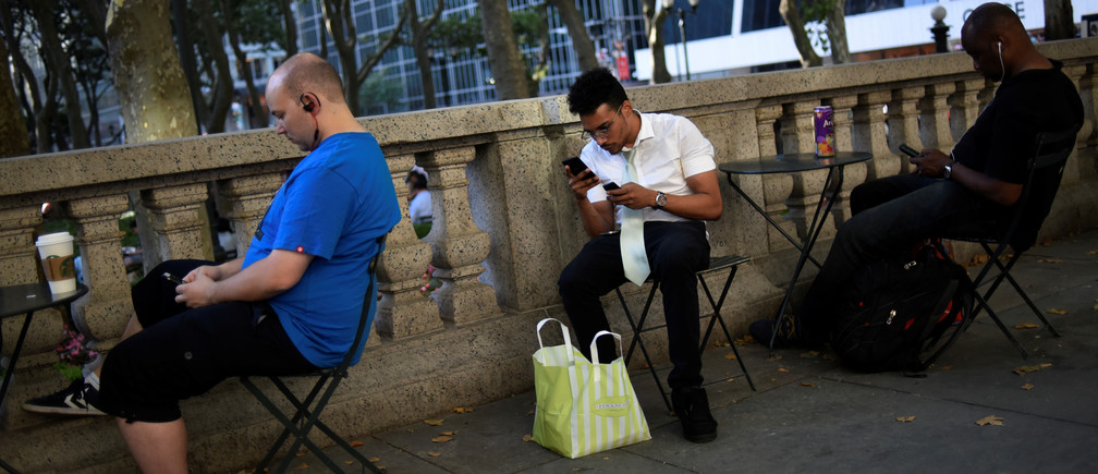 """David Melendez (C) uses three phones as he plays the augmented reality mobile game """"Pokemon Go"""" by Nintendo in New York City, U.S. July 11, 2016."""