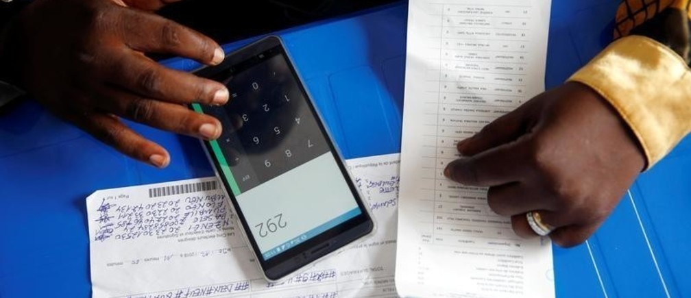 An official from Congo's Independent National Electoral Commission (CENI) uses his phone to calculate the numbers of presidential election votes at tallying centre in Kinshasa, Democratic Republic of Congo, January 4, 2019. REUTERS/Baz Ratner - RC191796EC90