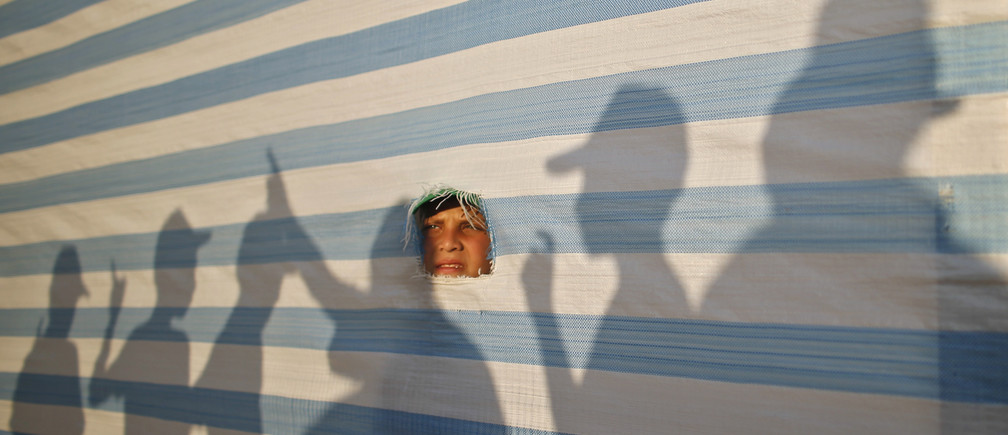 A Palestinian boy looks on through a fabric sheet as he takes part in a summer camp organized by the Hamas movement in Gaza City June 16, 2013.