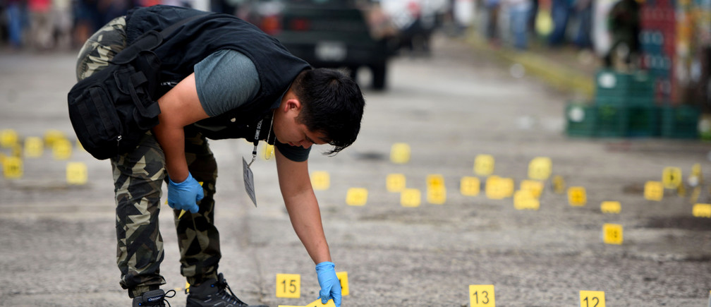 A forensic technician looks for bullet casings after a shootout in the Mexican state of Veracruz.