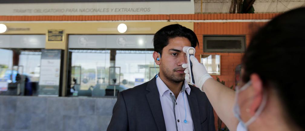 Un trabajador de la salud le toma la temperatura a un hombre en el cruce fronterizo de Puerto Falcón, después de que el gobierno cerrara las escuelas y suspendiera los eventos a gran escala durante un período de 15 días debido al brote de coronovirus, en Puerto Falcón, Paraguay, el 11 de marzo de 2020.