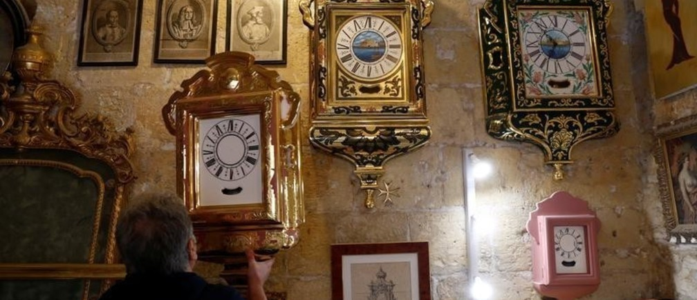 """Gilder Pierre Darmanin, sole owner of his family business Ditta Darmanin which stretches back six generations, lifts a traditional Maltese clock, known as the """"Arlogg Tal-Lira"""" ('pound clock'), off the wall at his workshop in Valletta, Malta, January 30, 2018."""