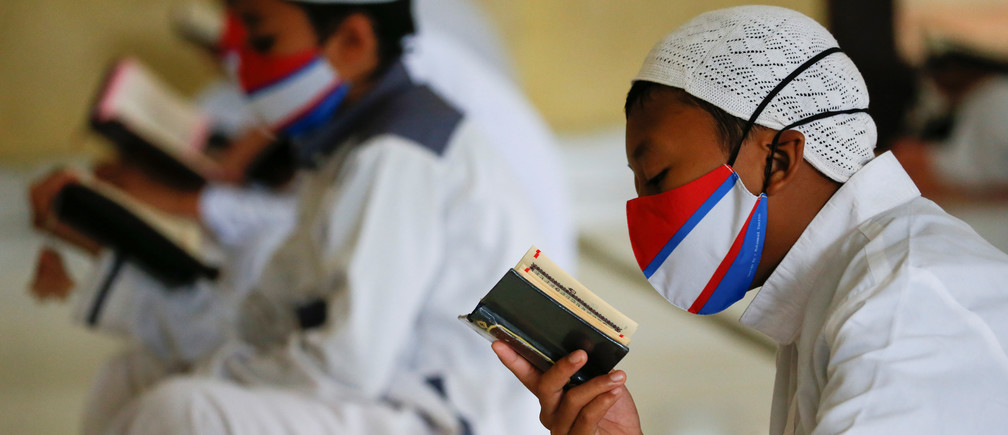 Muslim students wearing face masks practice social distancing while reading Koran at Daarul Qur'an Al Kautsar boarding school mosque, amidst the spread of the coronavirus disease (COVID-19) during the holy fasting month of Ramadan, in Bogor, West Java province, Indonesia, May 9, 2020. REUTERS/Willy Kurniawan - RC2RKG98H7JC