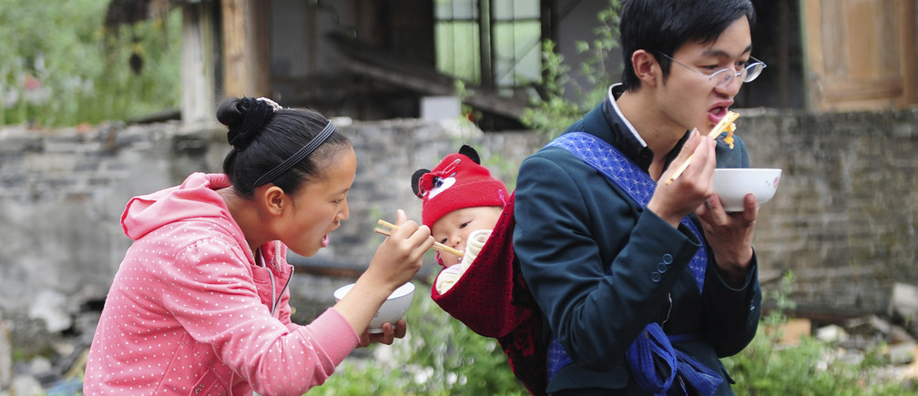 A mother feeds her child, who is being carried by the father, after last Saturday's earthquake hit Lushan county, Ya'an, Sichuan province, April 24, 2013. China has poured resources into Sichuan since the magnitude 6.6 quake hit early on Saturday, including 1 billion yuan ($161.9 million) for disaster relief and compensation. But mountainous terrain and poor infrastructure have made reaching victims difficult. The earthquake has left 196 dead, 21 missing and 11,470 injured, according to Xinhua News Agency. Picture taken April 24, 2013. REUTERS/Stringer (CHINA - Tags: DISASTER ENVIRONMENT TPX IMAGES OF THE DAY) CHINA OUT. NO COMMERCIAL OR EDITORIAL SALES IN CHINA - GM1E94Q11DF01