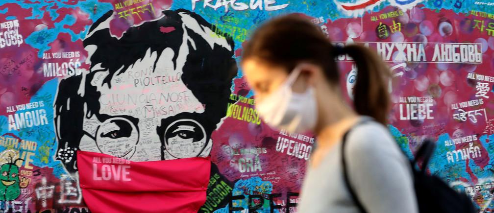 Una mujer con una máscara facial pasa por delante del legendario muro de John Lennon cubierto de graffitis mientras la propagación de la enfermedad coronavirus (COVID-19) continúa en Praga, República Checa, el 6 de abril de 2020.