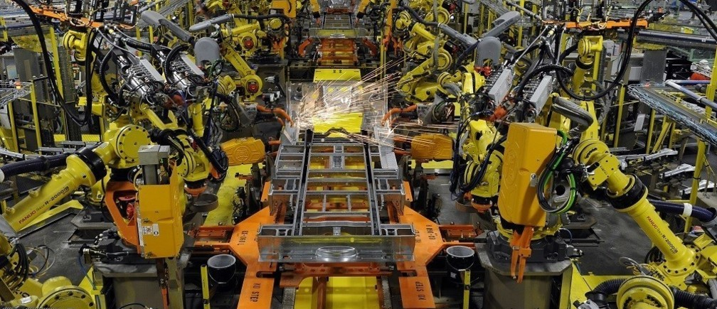 Robotic arms spot welds on the chassis of a Ford Transit Van under assembly at the Ford Claycomo Assembly Plant in Claycomo, Missouri April 30, 2014.  REUTERS/Dave Kaup  (UNITED STATES - Tags: BUSINESS TRANSPORT) - RTR3NB56