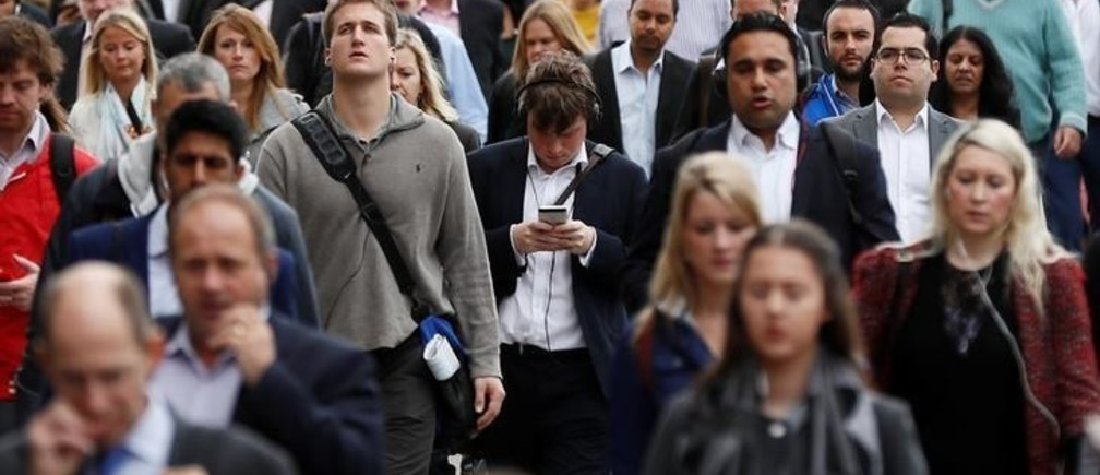 """A commuter looks at his mobile phone as he crosses London Bridge during rush hour in London, Britain September 27, 2016. REUTERS/Stefan Wermuth SEARCH """"WERMUTH PHONES"""" FOR THIS STORY. SEARCH """"THE WIDER IMAGE"""" FOR ALL STORIES."""