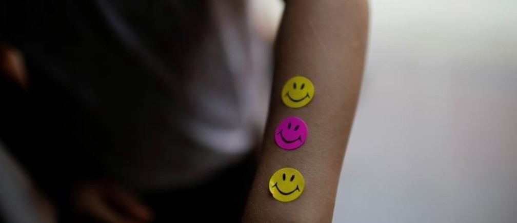 "A child shows smiley stickers he received after taking a blood test sample during a health program of the NGO ""Comparte por una vida"" (Share for a life) at La Frontera school in Cucuta, Colombia February 5, 2019. Picture taken February 5, 2019. REUTERS/Marco Bello - RC1B599549B0"